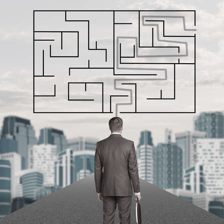 way out: Businessman with suitcase and labyrinth on cityscape background, back view Stock Photo