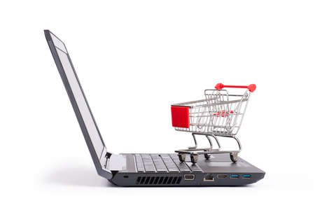 close up view: Shopping cart on laptop on isolated white background, close up view
