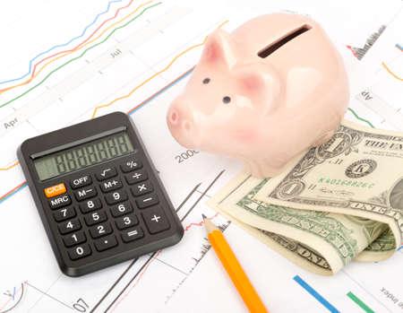 banco dinero: Hucha con dinero en efectivo y calculadora en documentos de negocios de fondo