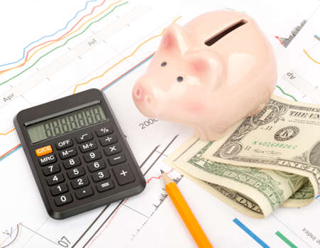 piggy bank: Piggy bank with cash and calculator on business documents background
