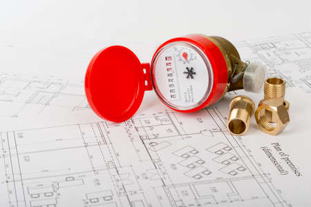 red water: Red water meter with fitting pieces on draft background Stock Photo
