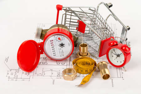 close fitting: Water meter with shopping cart and pipe fittings on draft background