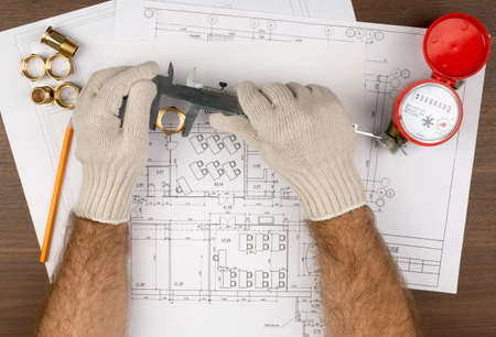 fitting in: Mans hands in gloves holding trammel and pipe fitting on draft background