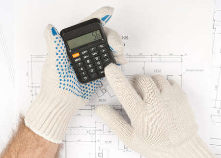 mans: Mans arms in gloves holding calculator on draft background