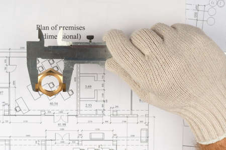 close fitting: Mans hand in glove holding trammel and pipe fitting on draft background