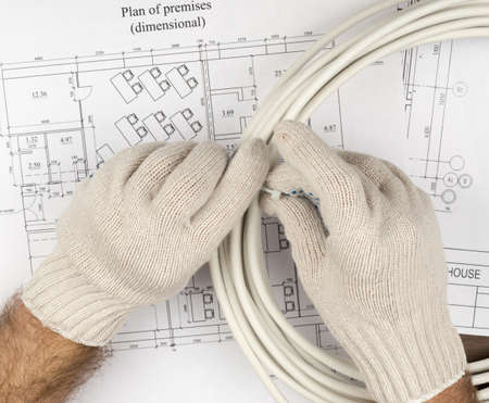 mans: Mans hands fixing wires on draft background