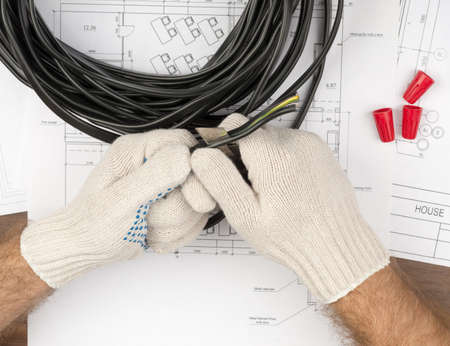 cable cutter: Mans hands holding cable and cutter on draft background Stock Photo