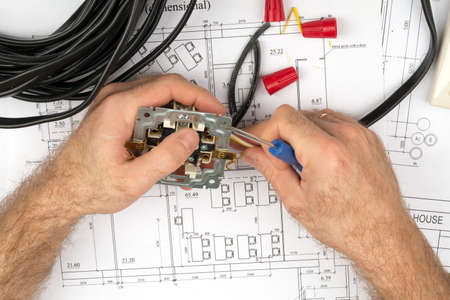mans: Mans hands fixing socket with screwdriver on draft background Stock Photo
