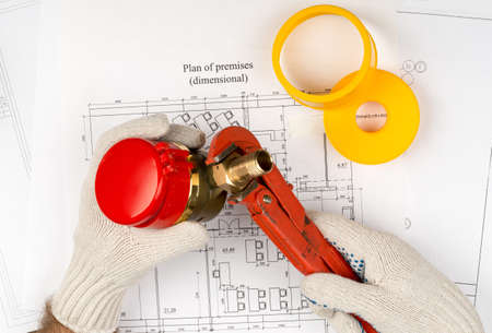 close fitting: Mans hands in gloves holding water meter on draft background