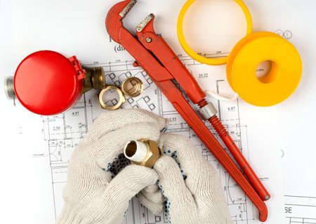 pipe fitting: Mans hands in gloves holding pipe fitting on draft background