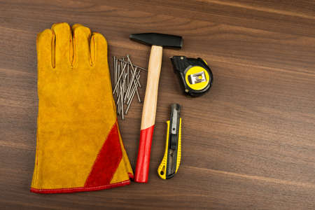 nail cutter: Construction gloves with hammer and nails on wooden table