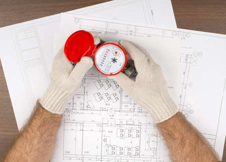 mans: Mans hands in gloves holding water meter on draft background