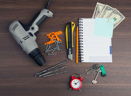 copybook: Drill with money and copybook on wooden table Stock Photo