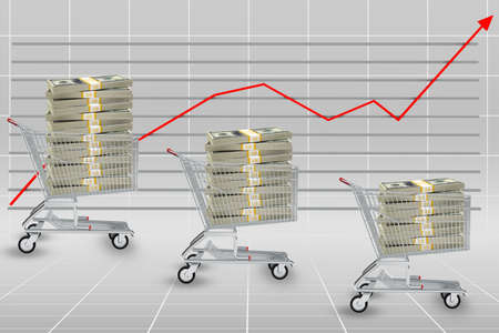 graphical: Stack of dollars in shopping cart on graphical chart background Stock Photo