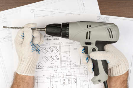 mans: Mans hands in gloves holding drill on draft background