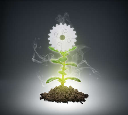 puzzle background: Heap of ground with plant and puzzle parts wheel on grey background Stock Photo