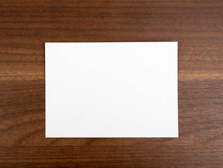table top: Blank card on wooden table, top view