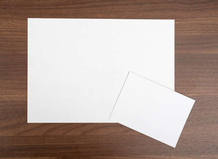 wooden table top view: Blank sheets on wooden table, top view