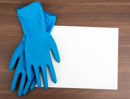 rubber gloves: Blank paper with rubber gloves on wooden table