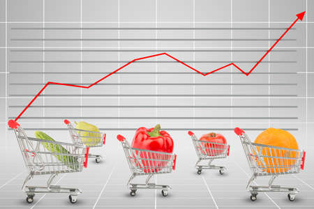 graphical: Vegetables and fruits in shopping carts on graphical chart background Stock Photo