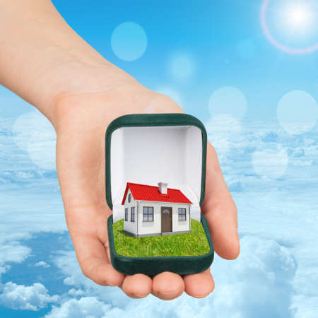open  women: Empty ring box house in humans hand on blue sky background