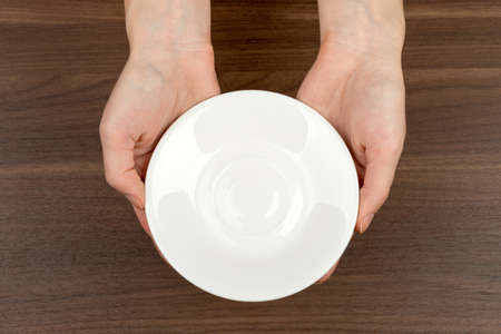 womans: Womans hands holding saucer on wooden table background