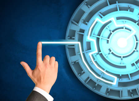 holographic: Businessmans hand touching holographic screen with labyrinth Stock Photo