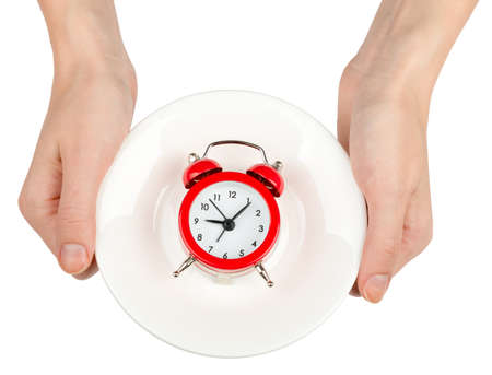 womans: Womans hands holding saucer with alarm clock on isolated white background