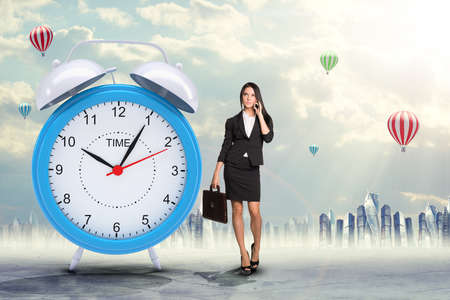 lady on phone: Lady talking on cell phone with big alarm clock on city background Stock Photo