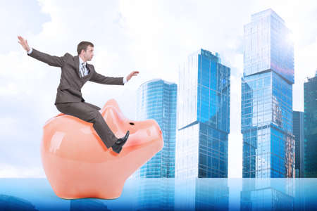 councilor: Businessman sitting on piggy bank on city background