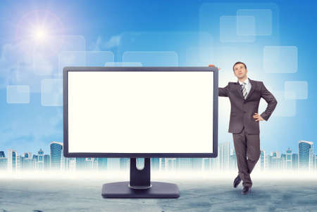 councilor: Businessman leaning on monitor on cityscape background Stock Photo