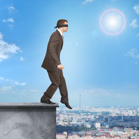 councilor: Man walking from edge of building roof with band on his eyes Stock Photo