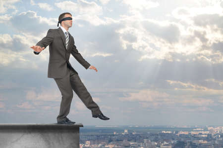 councilor: Man stepping from edge of building roof with band on his eyes Stock Photo