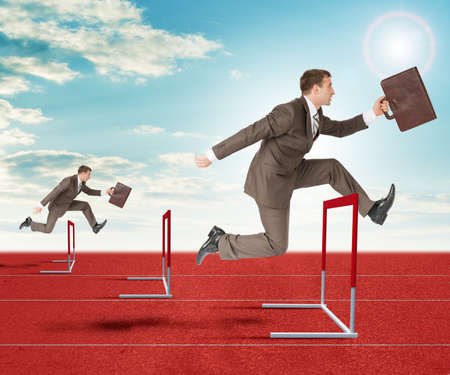 Businessmen with suitcase  hopping over treadmill barrier
