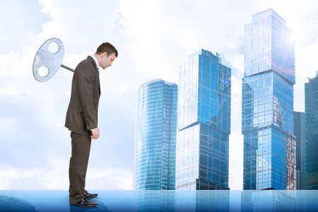 councilor: Businessman looking down with key in back with city background Stock Photo