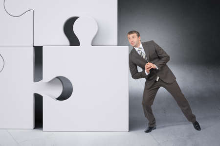 councilor: Businessman pushing puzzle piece on grey background