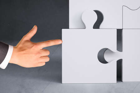 councilor: Businessman hand pushing puzzle piece on grey background Stock Photo