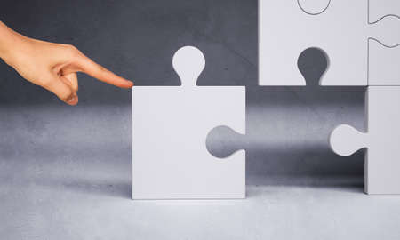 face work: Businessman hand pushing puzzle piece on grey background Stock Photo