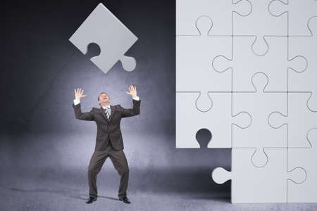 councilor: Businessman throwing on grey puzzle piece  on grey background