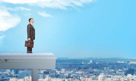 councilor: Businessman with suitcase standing on roof with city view