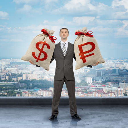 moneybag: Businessman holding big moneybag with dollar and ruble signs Stock Photo