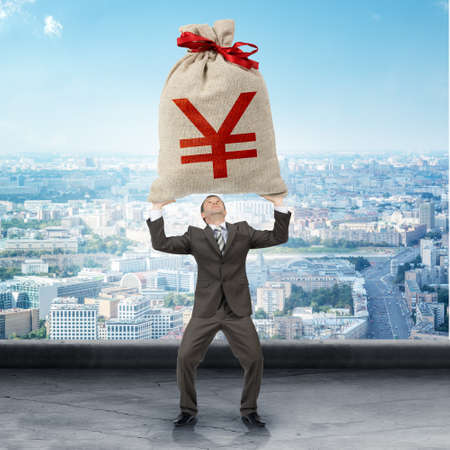 yen sign: Businessman holding big moneybag with yen sign with city view