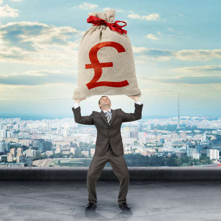 moneybag: Businessman holding big moneybag with pound sign with city view