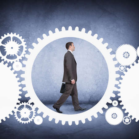 cog wheel: Businessman walking in cog wheel on abstract background