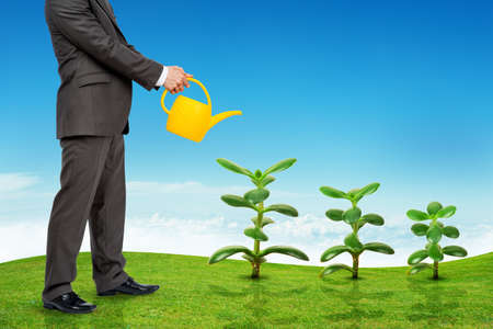 wateringcan: Businessman with watering-can and without head watering plants