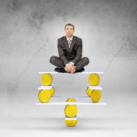 looking at camera: Businessman sitting on balance with gold coins and looking at camera