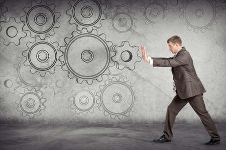 cog wheel: Businessman pushing cog wheel on abstract background