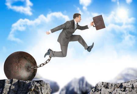 bottomless: Businessman with suitcase and iron ballast  hopping over bottomless pit Stock Photo