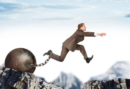 Businessman with iron ballast  hopping over bottomless pit Stock Photo