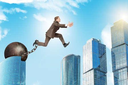 ballast: Businessman with iron ballast hopping over city Stock Photo